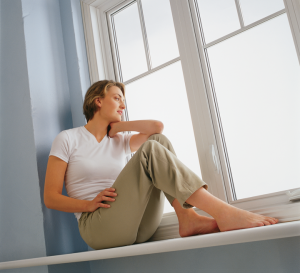 A woman sits beside a large casement window on a deep ledge, looking out the window.