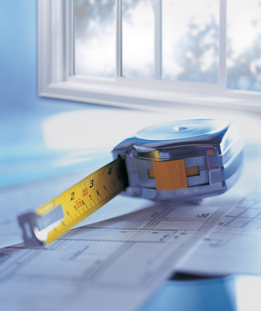 Medium shot of a tape measure sitting on blueprints beside a window.