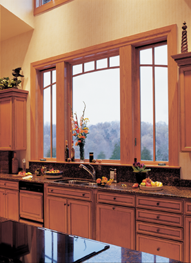 Wooden casement windows in a kitchen overlooking hills.