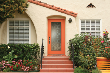 The exterior of a home with trim hedges and an orange front door