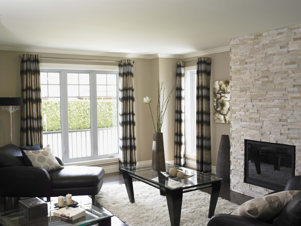 A squished looking living room with large vinyl windows.