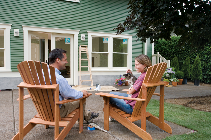 Lifestyle image of a middle-aged couple sitting on lawn chairs beside a house undergoing window and door renovations.