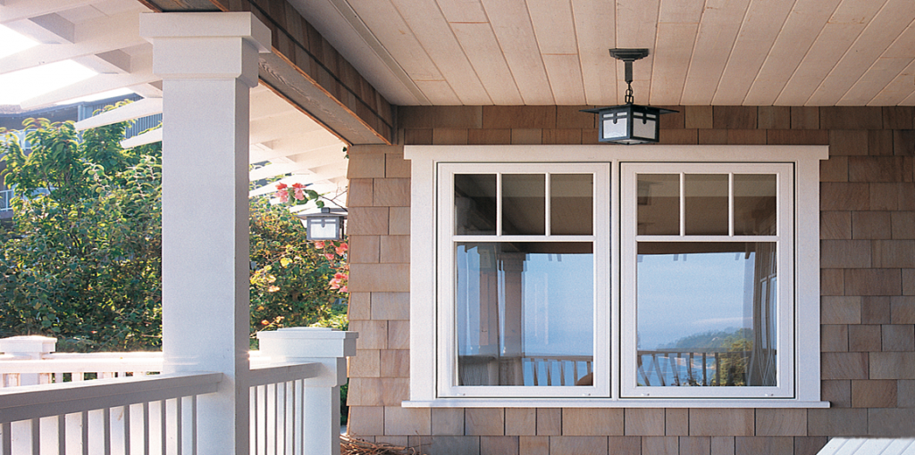 Image of new side-by-side vinyl windows, including a transom with 2 grilles and 3 panes, facing onto a verandah.