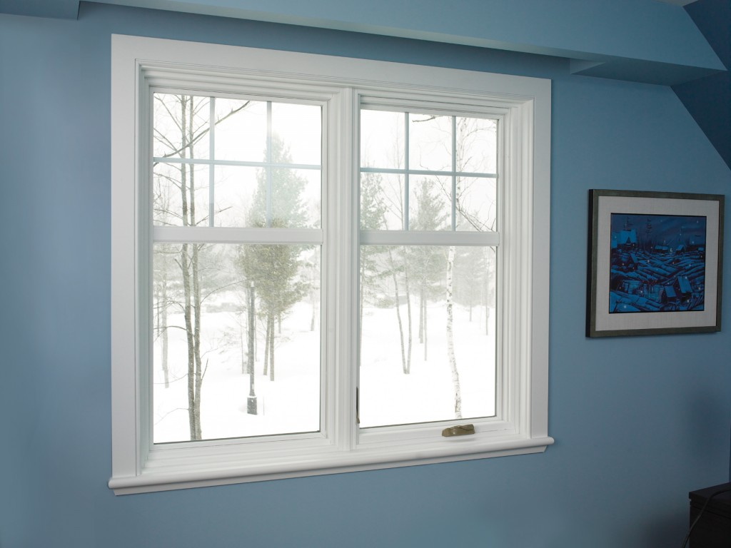 Image of a large vinyl fixed window looking out over a snow-covered tree on a winter day.