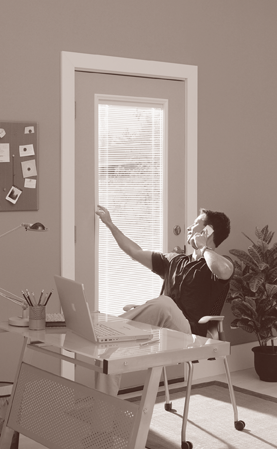 Sepia-toned image of a man at a desk talking on the phone while looking out of a patio door.
