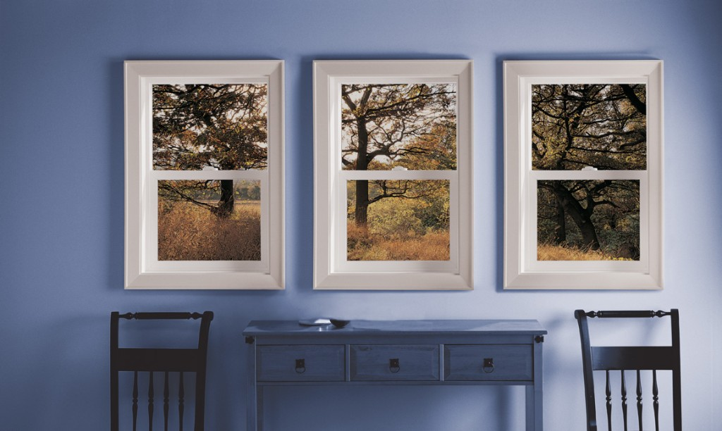 Image of 3 side-by-side vinyl, single-hung windows in a blue bedroom facing an autumn outdoor setting.