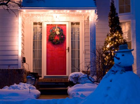 Image de l'extérieur d'une maison bien décoré avec sur la façade une porte d'entrée rouge, une couronne et un bonhomme de neige dans le jardin.