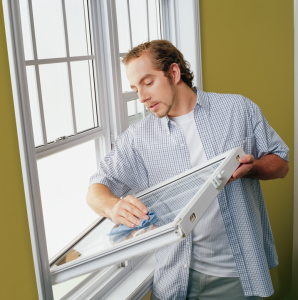 Image of a young man cleaning a window pane that he has removed from the frame.