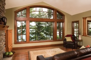 Wood casement windows combined with wide fixed windows with matching wood grilles overlooking a forest.