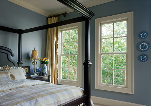 Double-hung windows in a bedroom overlooking trees.