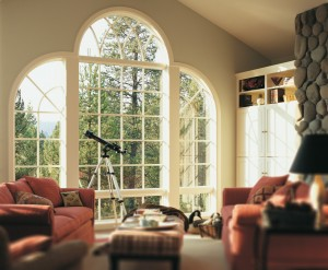 A wide custom window arrangement letting natural light into a dark room.