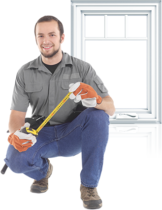 A young male window contractor squatting with a measuring tape in front of a casement window.