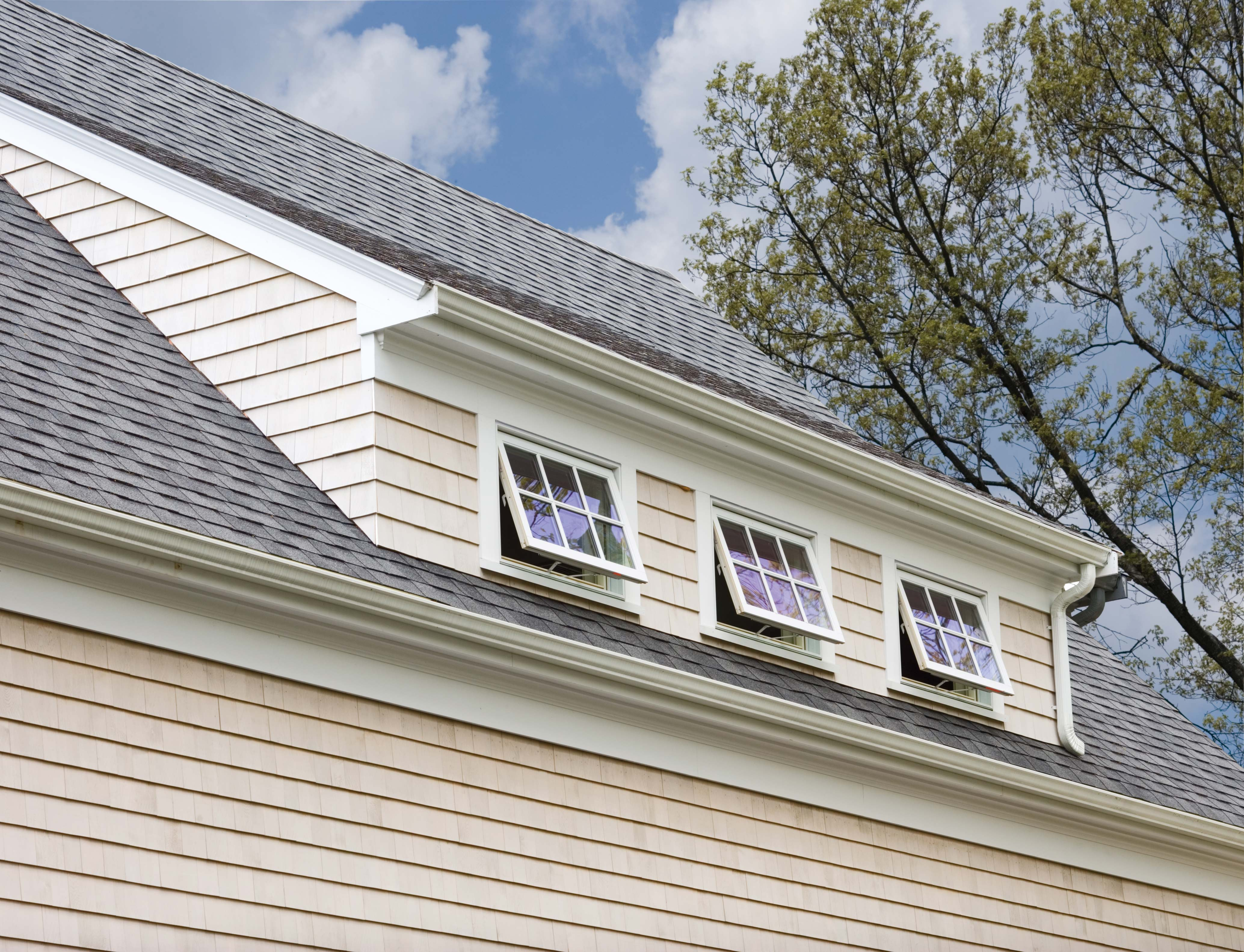 Outside shot of three open awning windows on a sloped roof.
