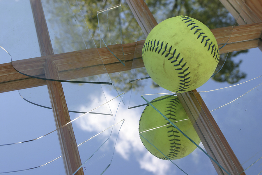 Picture of a baseball on a broken window.