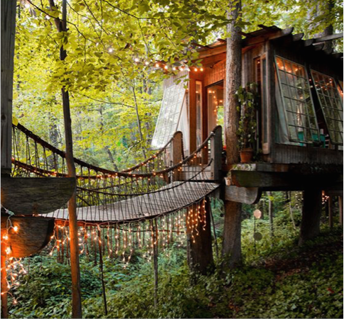 Rustic treehouse with large, repuposed criss-crossed windows, featuring a wooden bridge and small string-lights.