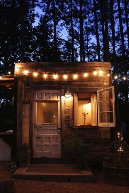 Ground-level treehouse with repurposed door and swing-open window. Cascading string-lights on face of treehouse are seen.