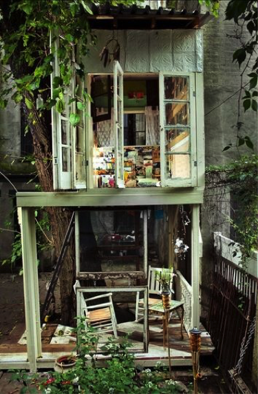 A lightly-coloured, two-story, ground-level backyard treehouse featuring shutter-style windows.
