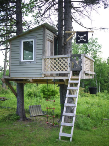 A treehouse with a small glass window featuring a pirate flag and two ladders; one is a white ladder and one is a rope ladder.