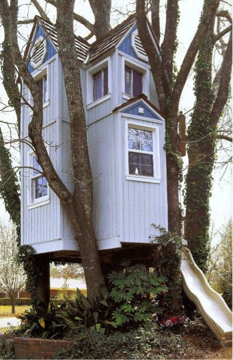A grand two-story, fully enclosed treehouse with a fully shingled roof and glass windows.