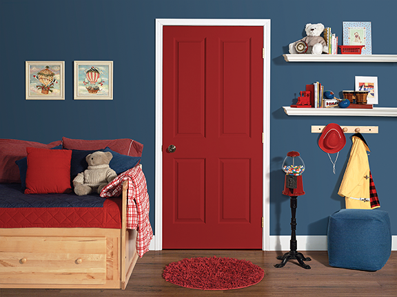 Red door in a child's bedroom with blue wallpaper