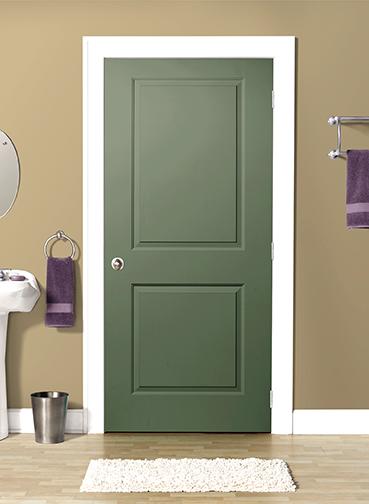 Green closed interior door in a bathroom with beige wallpaper