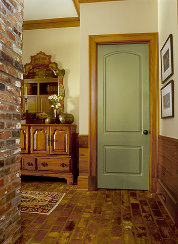Moss green interior door in room with brick.