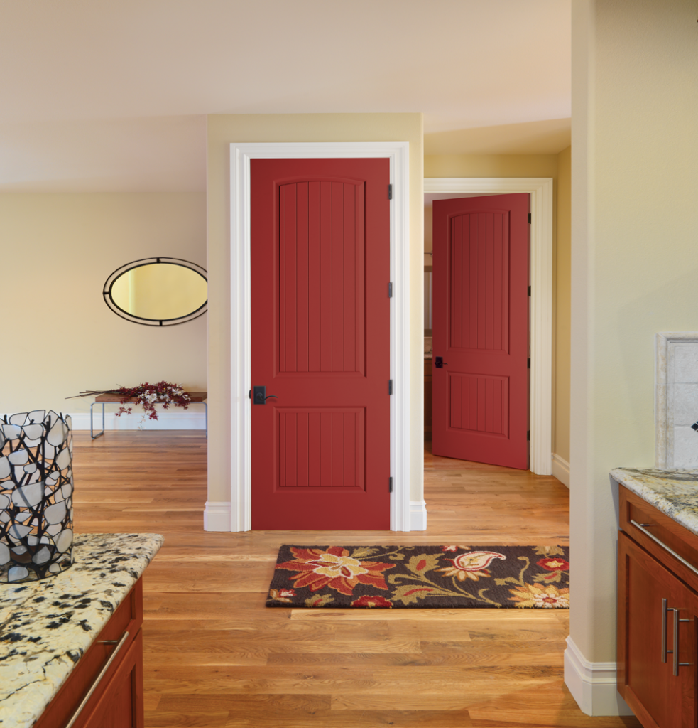 Two red interior doors in a bedroom with hardwood floors.