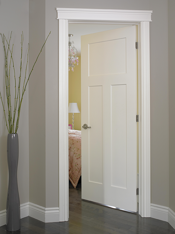 Ajar white interior door in a room with gray wallpaper.