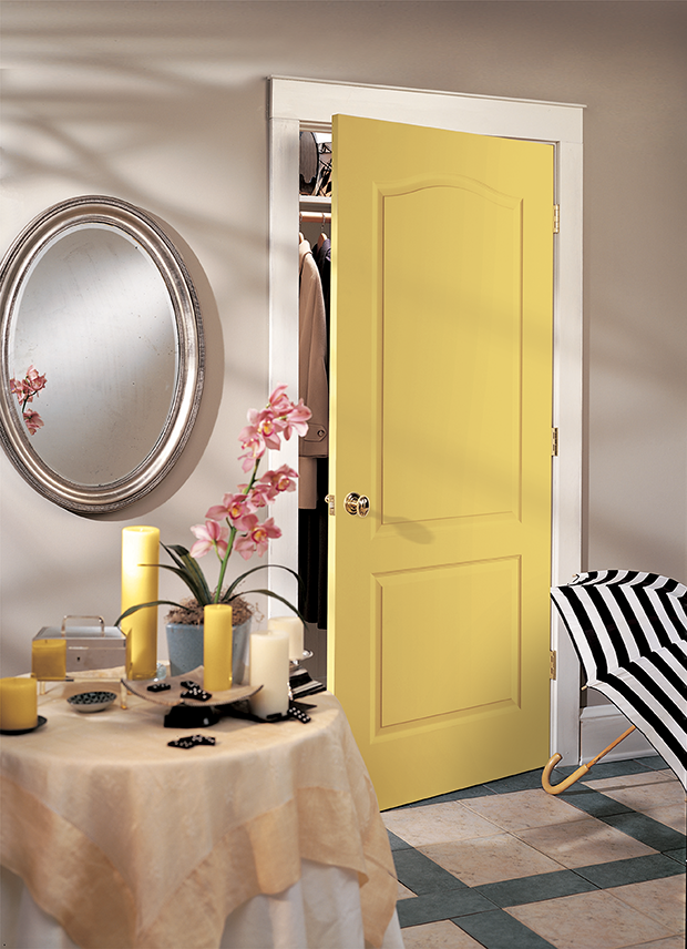 Yellow interior door slightly ajar in room with rounded mirror.